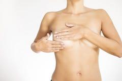 Kvinna som testar hennes bröst för cancer Arkivbilder