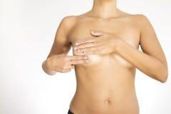 Kvinna som testar hennes bröst för cancer Royaltyfri Foto