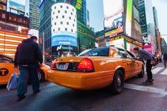 Kvinna som tidvis tar en gul fyrkant för taxi, NYC Royaltyfria Bilder
