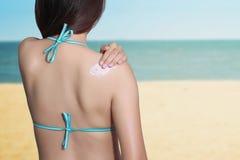 Kvinna som tillbaka applicerar sunscreen på henne med havsbakgrund Royaltyfri Foto
