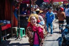 Kvinna som tillbaka bär en behandla som ett barn på henne Royaltyfri Foto