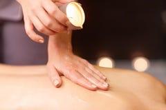 Kvinna som tillbaka gör massage med varm olja på brunnsorten royaltyfri bild