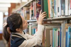 Kvinna som tillbaka sätter boken på en bokhylla Royaltyfria Bilder