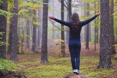 Kvinna som tillber med öppna armar i en dimmig skog för höst med gröna och röda sidor för guling, royaltyfria bilder