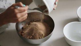 Kvinna som tillfogar ingredienser till en bunke för att laga mat hem- gjord choklad stock video