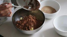 Kvinna som tillfogar ingredienser till en bunke för att laga mat hem- gjord choklad arkivfilmer