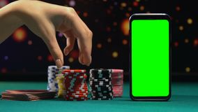 Kvinna som tillfogar tecknet till den stora högen, smartphone med den gröna skärmen, online-kasino arkivfilmer