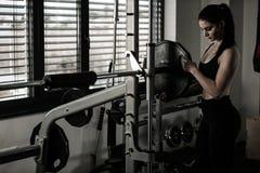 Kvinna som tillfogar vikt på en stång som henne genomkörare i konditionidrottshall royaltyfria bilder