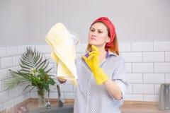 Kvinna som torkar exponeringsglas med handduken i k?k fotografering för bildbyråer