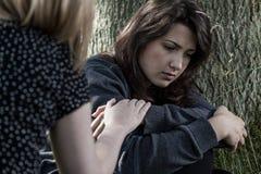 Kvinna som tröstar hennes ledsna vän Arkivfoto