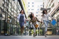 Kvinna som tre går den lyckliga och tillfredsställda stadsgatan efter shoppi arkivbilder