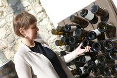 Kvinna som trycker på den tomma vinflaskan arkivfoton