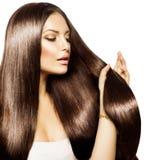 Kvinna som trycker på hennes långa hår Fotografering för Bildbyråer