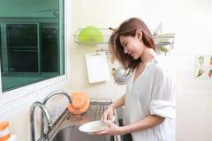 Kvinna som tvättar disken i diskho i hus Arkivfoto