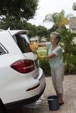 Kvinna som tvättar vindrutan av en vit salongbil Arkivfoto