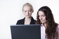 Kvinna som två ser datorskärmen royaltyfria bilder