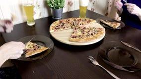 Kvinna som två sitter vid tabellen, äter pizza och dricker öl Familjmatställebegrepp arkivfilmer