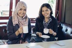 Kvinna som två talar, medan tycka om kaffe Fotografering för Bildbyråer