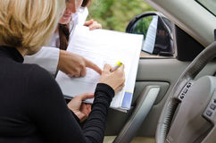 Kvinna som två undertecknar ett avtal för att inhandla en bil Royaltyfri Foto