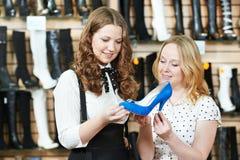 Kvinna som två väljer, skor i skodonlager Arkivbild