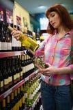 Kvinna som tvekar mellan två flaskor av vin Royaltyfri Bild