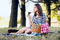 Kvinna som tycker om ögonblick med exponeringsglas av vin Arkivbild