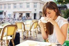 Kvinna som tycker om aromen av henne kaffe arkivfoto