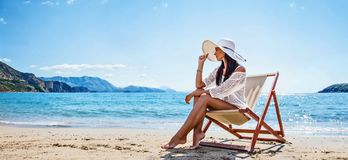 Kvinna som tycker om att solbada på stranden royaltyfria bilder