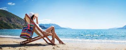 Kvinna som tycker om att solbada på stranden royaltyfri fotografi
