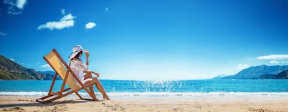 Kvinna som tycker om att solbada p? stranden royaltyfri bild