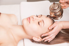 Kvinna som tycker om Ayurveda den olje- head massagen i brunnsort royaltyfria foton