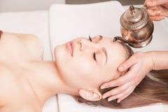 Kvinna som tycker om Ayurveda den olje- head massagen i brunnsort fotografering för bildbyråer