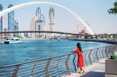 Kvinna som tycker om den Dubai sikten fr?n vattenkanalen royaltyfri fotografi