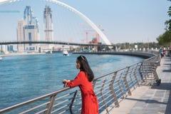 Kvinna som tycker om den Dubai sikten fr?n vattenkanalen royaltyfri bild