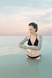 Kvinna som tycker om den mineraliska källan för naturlig gyttja på backgr för dött hav Royaltyfri Fotografi