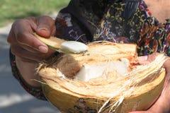 Kvinna som tycker om den nya kokosnöten Arkivbild