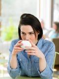 Kvinna som tycker om drinken i kafé Arkivbilder
