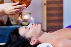 Kvinna som tycker om en behandling för Ayurveda oljamassage i en brunnsort royaltyfria bilder