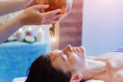 Kvinna som tycker om en behandling för Ayurveda oljamassage i en brunnsort royaltyfria foton