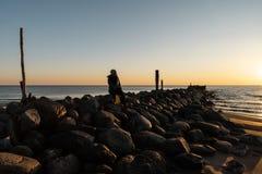 Kvinna som tycker om en kall vårsolnedgång på en stenblockstrand nära Östersjön royaltyfria bilder