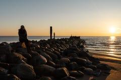 Kvinna som tycker om en kall vårsolnedgång på en stenblockstrand nära Östersjön fotografering för bildbyråer