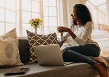 Kvinna som tycker om en kopp kaffe, medan arbeta på bärbara datorn royaltyfri foto