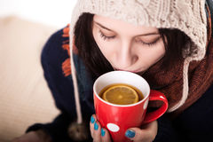 Kvinna som tycker om en stor kopp av nytt bryggat varmt te, som hon kopplar av på en soffa i vardagsrummet Royaltyfri Bild