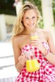 Kvinna som tycker om exponeringsglas av orange fruktsaft royaltyfri bild