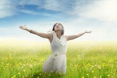Kvinna som tycker om frihet på blommafält Fotografering för Bildbyråer