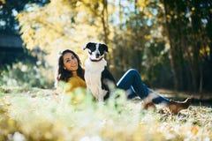 Kvinna som tycker om fritid med hennes hund arkivbild