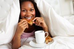 Kvinna som tycker om frukosten i säng arkivbild