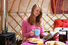Kvinna som tycker om frukoststunden som campar i traditionella Yurt Arkivbild