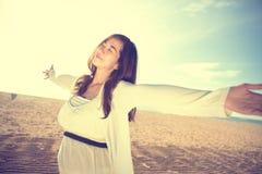 Kvinna som tycker om hennes tid i stranden Arkivbild