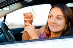 Kvinna som tycker om kaffe i henne bil Arkivfoton